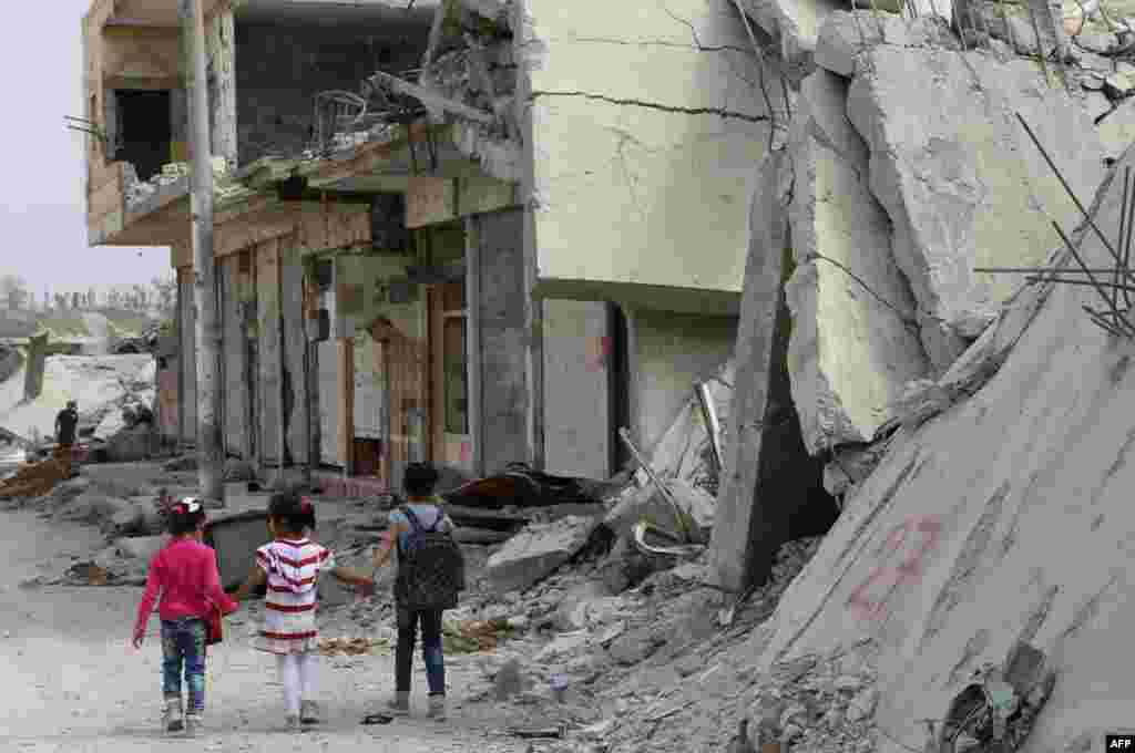 Syrian children walk past debris while heading to school on the second day of the new school year in the Kurdish town of Kobani. (AFP/Delil Souleiman)