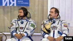 """Командир корабля """"Союз ТМА-8"""" Павел Виноградов и первый бразильский космонавт Маркеш Понтеш (справа налево) на примерке скафандров."""