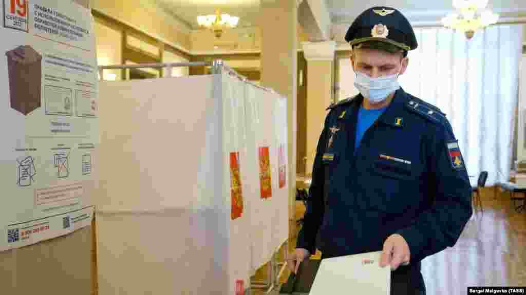 Российский военнослужащий во время голосования на выборах на избирательном участке №99, Севастополь