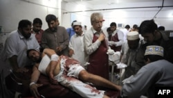 Paramedics treat an injured man in a hospital in Peshawar after a suicide blast in Mardan on June 18.