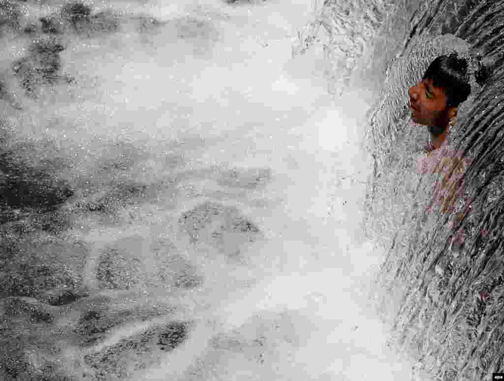 A Kashmiri boy cools himself under a waterfall to beat the heat on a hot day on the outskirts of Srinagar, the summer capital of Indian Kashmir. (epa/Farooq Khan)