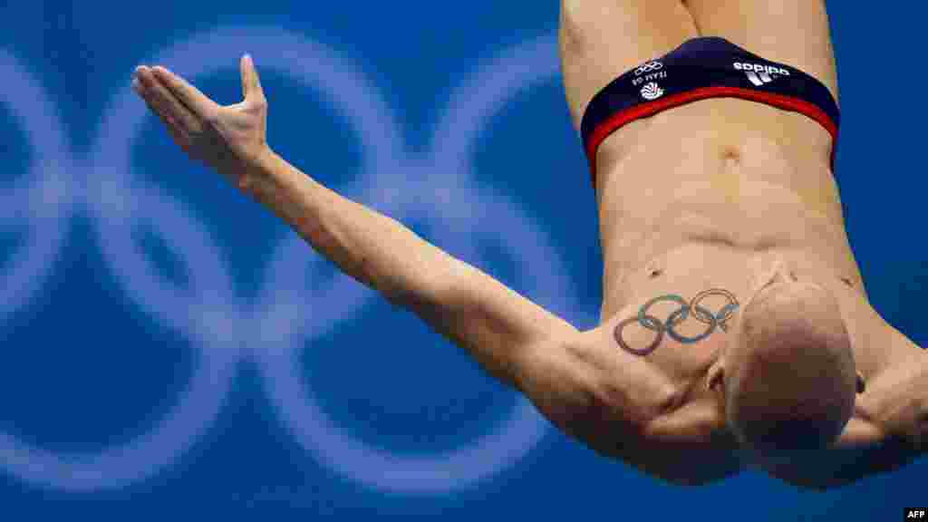 British athlete Nicholas Robinson Baker's tattoo of the Olympic rings is seen as he dives during a training session at the Aquatics Center in London on July 26. (AFP/Fabrice Coffrini)