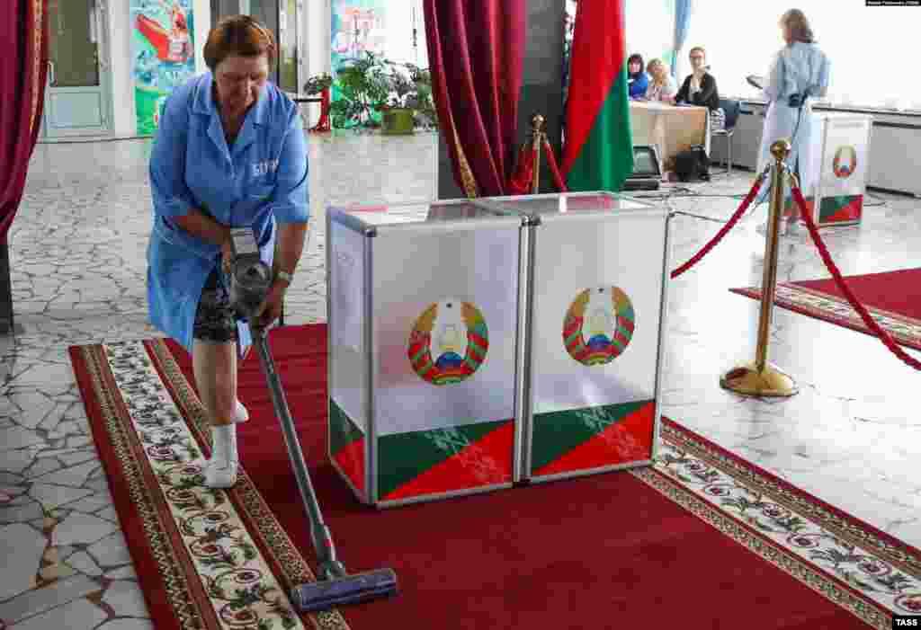 Прибиральниця чистить пилососом килим біля виборчих урн в Мінську
