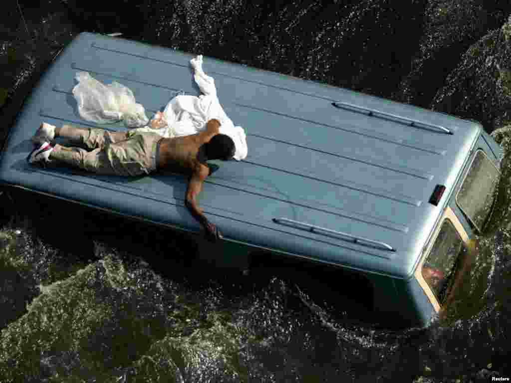 A man clings to the top of a vehicle surrounded by flood water before being rescued by the U.S. Coast Guard in New Orleans.