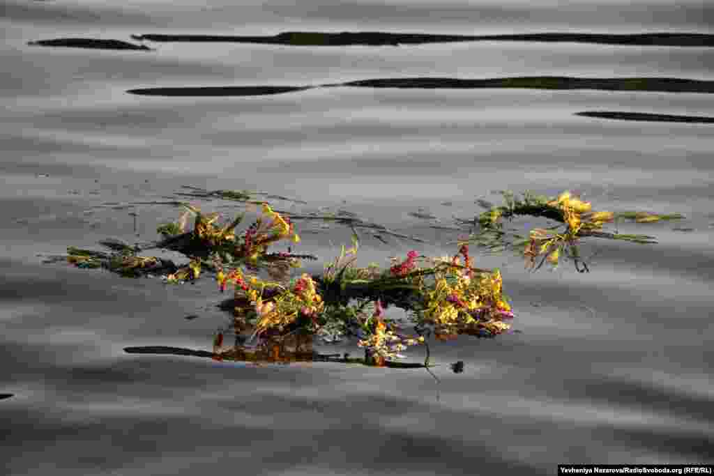 A wreath floats on the Dnieper River. Young women place wreaths on the water for divination: the direction they float is said to show where each woman's future husband lives.