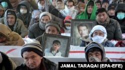Members of Pakistan's Shi'ite Hazara community gather around the coffins of victims on January 8 to mark the fifth day of protest in the outskirts of Quetta.