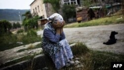 ქალი ტირის საკუთარი დანგრეული სახლის წინ. გორი, 2008 წლის 23 სექტემბერი.