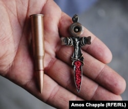 The jeweler holds a crucifix made from a sniper round.