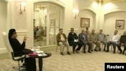Ливия жетекшісі Муамар Каддафидің (сол жақта) бір топ адаммен кездескені мемлекеттік телеарнадан көрсетілді. 11 мамыр 2011 жыл.