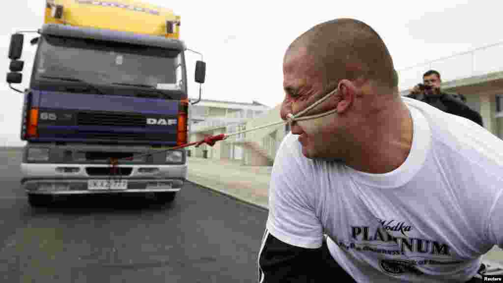Lasha Pataraya pulls an eight-ton truck with his ear in Rustavi, outside Tbilisi, Georgia. The 32-year-old sportsman will attempt to break a record registered by the Guinness Book of World Records by the end of the month, according to organizers. (Reuters/David Mdzinarishvili)