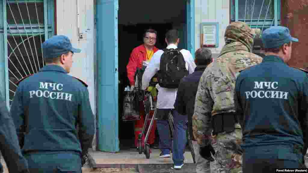 Медики транспортируют раненных в больницу после нападения на политехнический колледж в Керчи