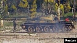 Солдат стоит у танка в окрестностях Хомса. 12 февраля 2012 года.