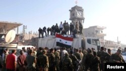 Government soldiers and civilians gather as they place the Syrian national flag on a truck in Qusayr on June 5.