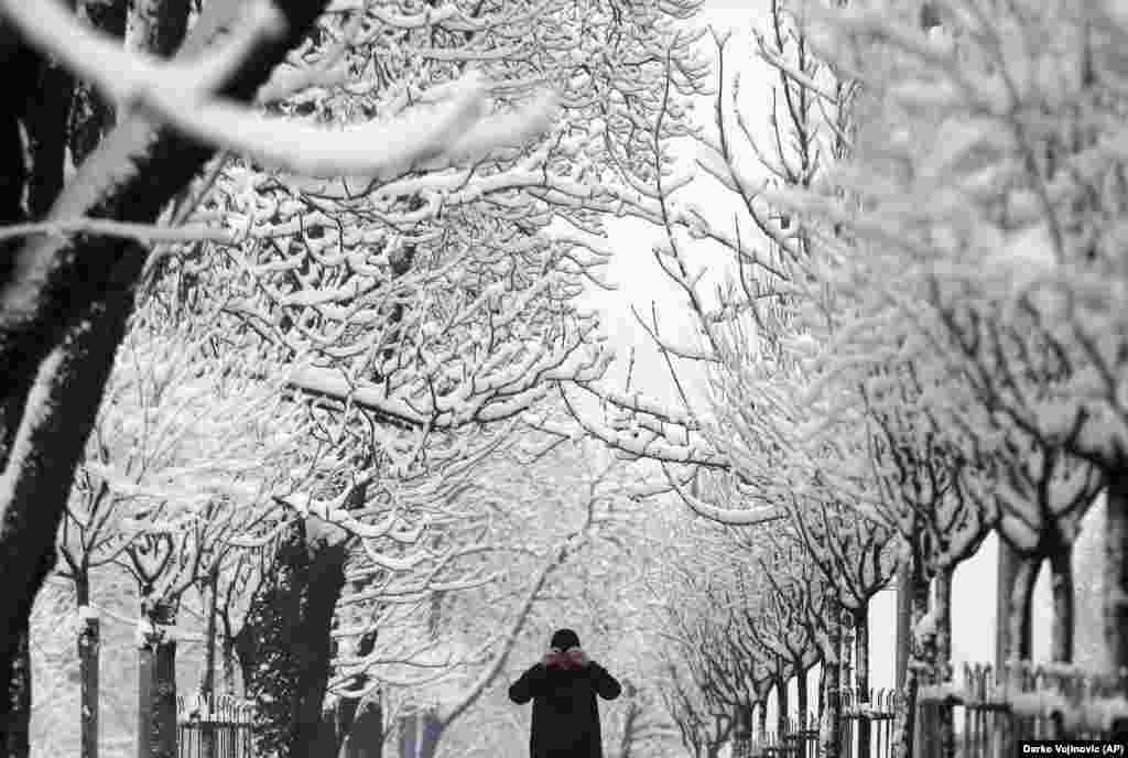 A man adjusts his hat on a snow-covered street in Belgrade. Meteorologists predict heavy snowfall and subzero temperatures in Serbia throughout the week. (AP/Darko Vojinovic)