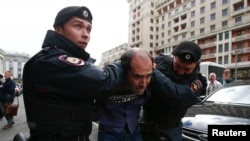 Interior Ministry officers detain a man during a protest against the razing of the Soviet-era apartment blocks outside the State Duma in Moscow on June 14.