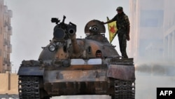 A fighter from the Kurdish People's Protection Units (YPG) drives a tank in the Al-Zohur nieighborhood in the Syrian city of Hasakeh.