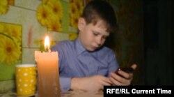 Egy orosz kisfiú készíti a házi feladatát áramszünet alatt