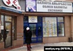 Люди стоят у пункта обмена валюты. Астана, 11 февраля 2014 года.