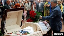Ukrainian President Petro Poroshenko lays flowers on the coffin containing the body of journalist Pavel Sheremet, who was killed by a car bomb, during a memorial service in Kyiv on July 22.