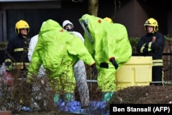 Officials in biohazard suits work near the bench in Salisbury where the Skripals were found.