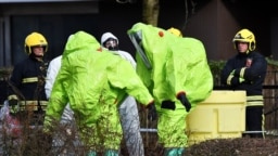 U.K. -- Members of the fire brigade are helped out of their green biohazard suits by colleagues in white protective coveralls after an operation to re-attach the tent over the bench where a man and a woman were found in critical condition sparking a major