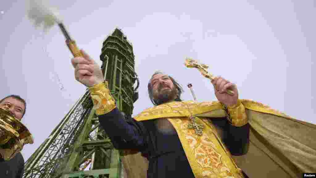 An Orthodox priest conducts a blessing service in front of the Soyuz TMA-06M spacecraft set up on its launch pad at the Baikonur cosmodrome in Kazakhstan. (Reuters/Shamil Zhumatov )