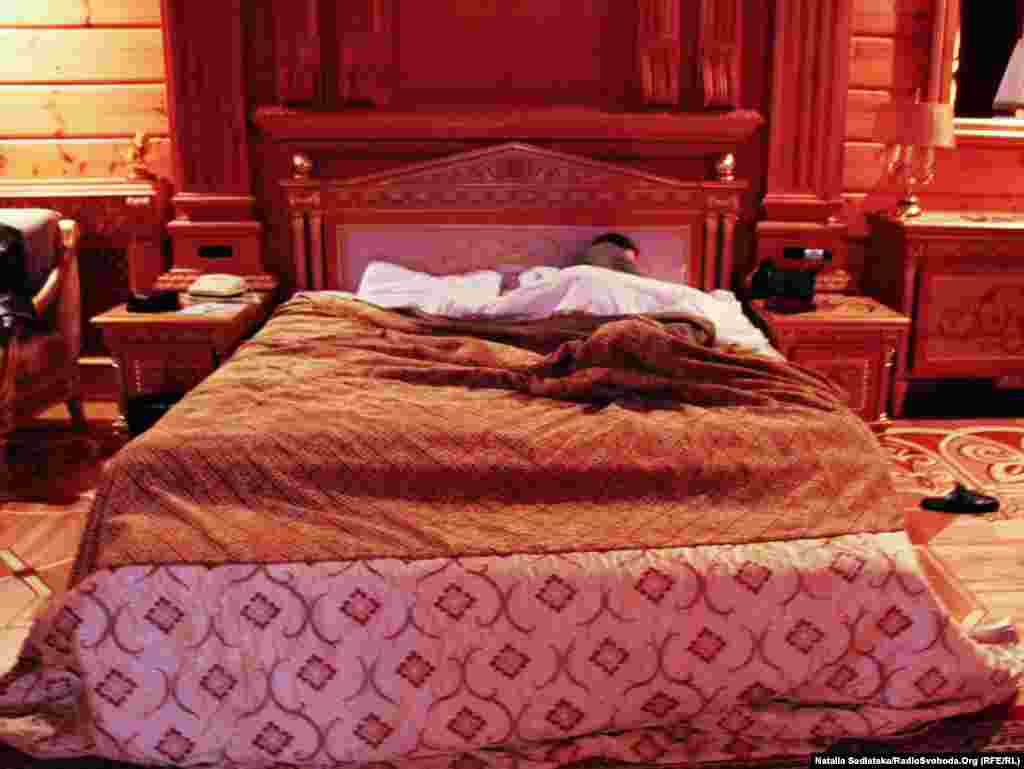 A visitor rests in the bedroom of ousted Ukrainian President Viktor Yanukovych at his hastily abandoned residence in Mezhyhirya, near Kyiv.