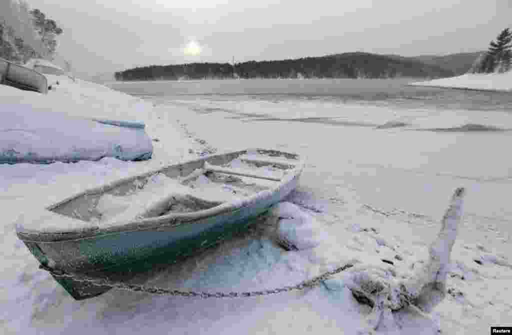 A Soviet-made plastic rowboat covered in snow and hoarfrost lies on a snowy bank of the Yenisei River, with the temperature at around minus 20 degrees Celsius, outside the Siberian city of Krasnoyarsk. (Reuters/Ilya Naymushin)