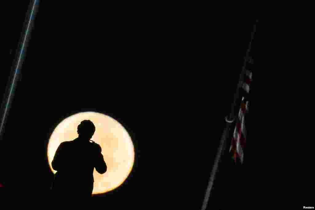Мужчина пытается сделать фото «суперлуния» над Национальным Молом в Вашингтоне.