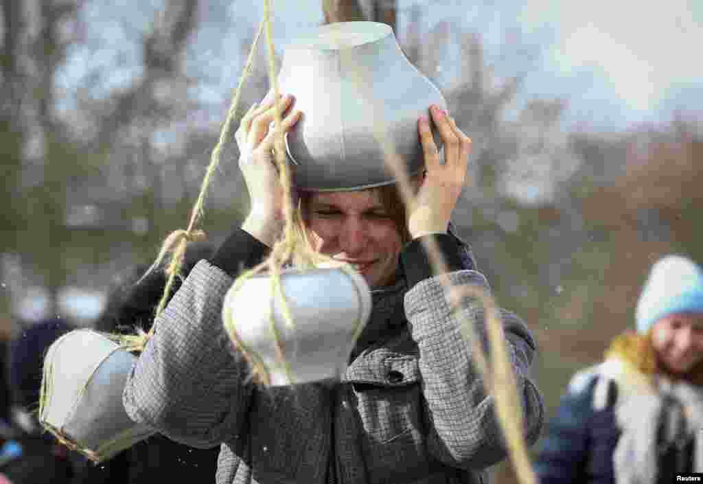 Мужчина принимает участие в конкурсе с горшочками на Масленицу. Озерцо, Беларусь