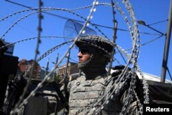 A U.S. soldier, part of a NATO peace force, places barbed wire on his Humvee during a protest in the ethnically divided town of Mitrovica. (file photo)