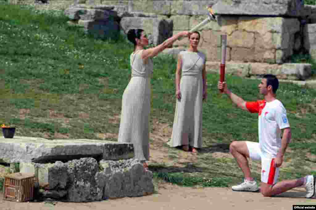 Greece - Actress Maria Nafpliotou, kindles a torch in hand of Greece's Olympic silver medallist for taekwondo Alexandros Nikolaidis during the Olympic flame lighting ceremony for the Beijing 2008 Games in Olympia, 24Mar2008