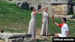 Актриса Мария Нафплиоту зажигает факел в луках серебряного призера Олимпийских игр по тэквондо Александроса Николаидиса