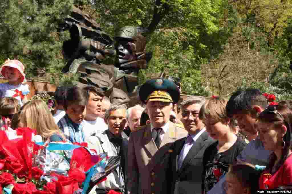 ЖСДП басшысы Жармахан Тұяқбай (оң жақтан төртінші) мен генерал-майор Әмірбек Тоғысов (ортадағы әскери форма киген адам) Мәңгілік алауға гүл қоюға келді. Алматы, 9 мамыр 2014 жыл.