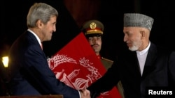Afghan President Hamid Karzai (left) and U.S. Secretary of State John Kerry (right) announced that they had reached a partial deal earlier this month.