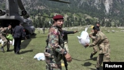 Pakistani military troops unload bags of grain from a U.S. Army helicopter delivering aid to the Khyber Pakhtunkhwa Province on August 5.