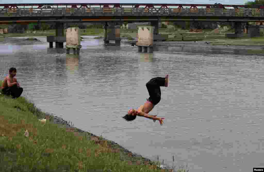 A man does a flip into the Sardaryab River on a hot day in Peshawar, Pakistan. (Reuters/Fayaz Aziz)