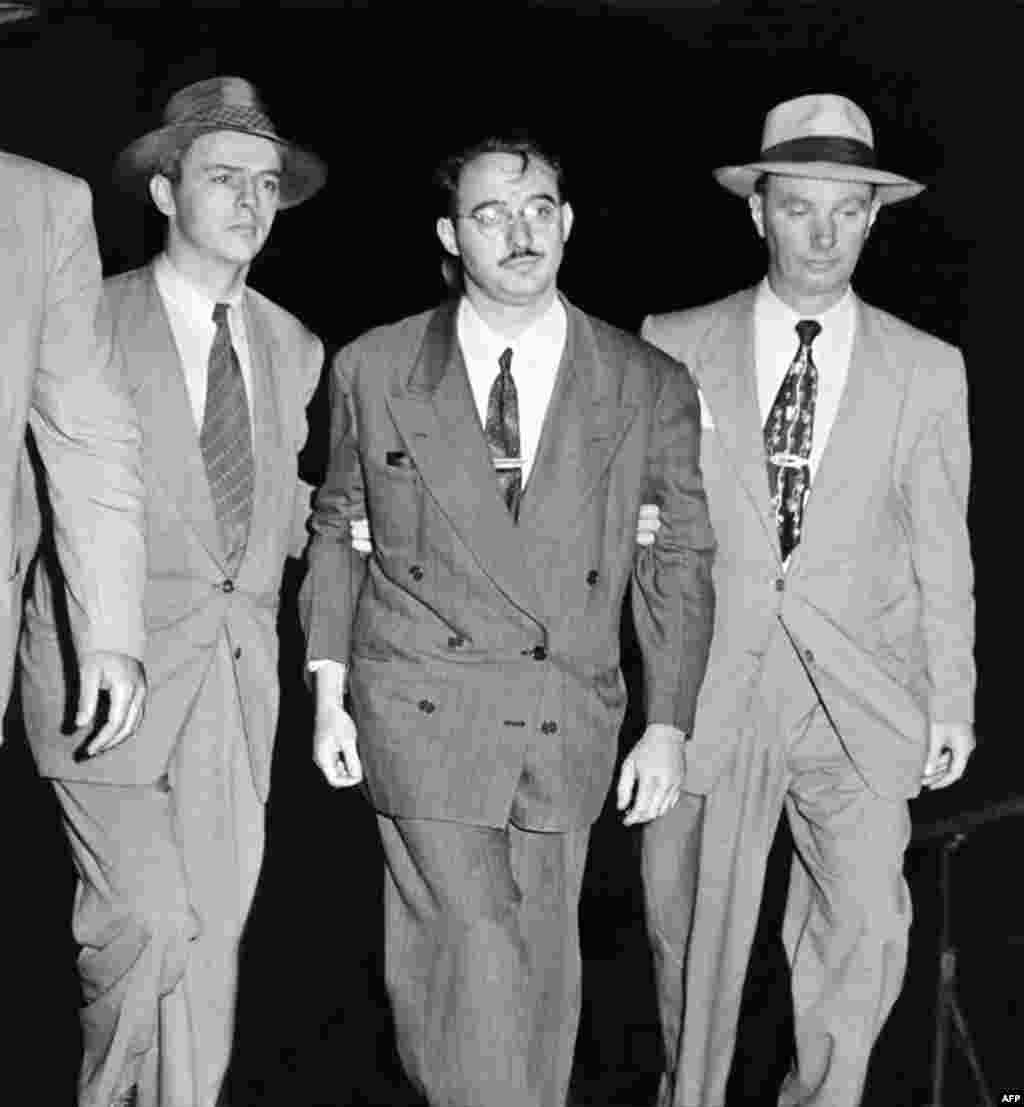FBI agents lead Julius Rosenberg away shortly after his arrest. His wife's brother, David Greenglass, had confessed to participating in a spy ring that he said included the Rosenbergs.