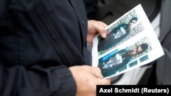A German policeman holds a picture of Jaber Al-Bakr.