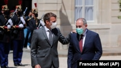 FRANCE -- French President Emmanuel Macron, left, welcomes Armenian acting Prime Minister Nikol Pashinian before a working lunch at the Elysee Palace in Paris, June 1, 2021