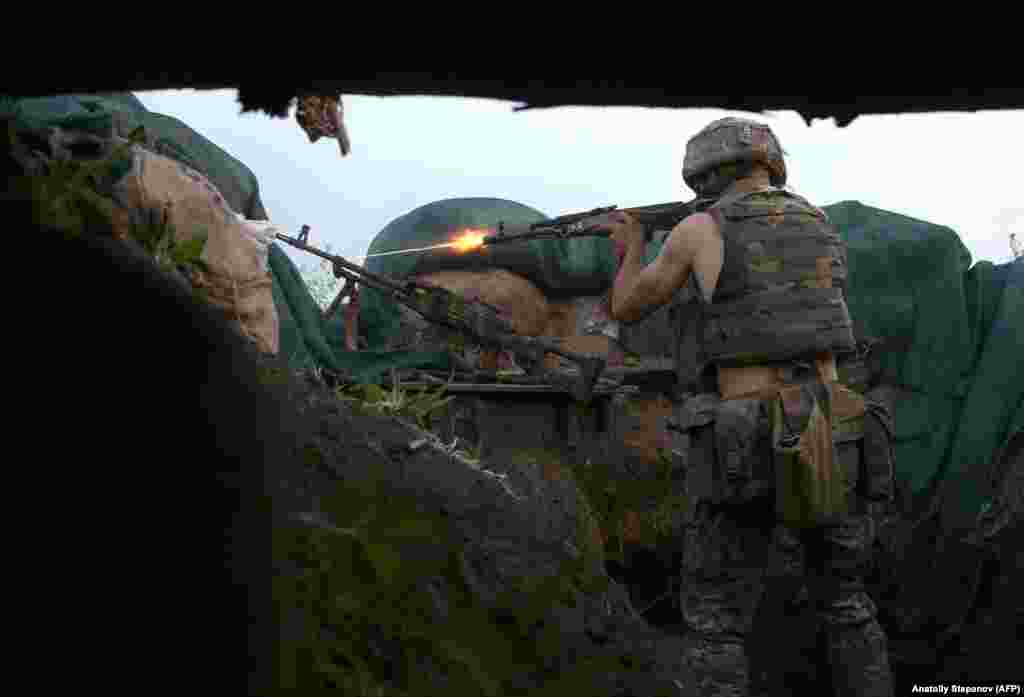 """A Ukrainian serviceman fires his rifle during clashes along the front line near Volnovakha in June 2021.  Having witnessed years of conflict in Ukraine, Stepanov calls the current state of the war a somewhat farcical routine in which both sides mostly hold to a """"cease-fire"""" until around 5 p.m. each day, when OSCE observers clock out, and then the shooting begins."""