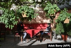 Young people sit at a sidewalk cafe in Kabul on June 19.