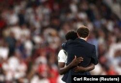 Managerul echipei Marii Britanii, Gareth Southgate, îl consolează pe Bukayo Saka după ce jucătorul a ratat lovitura de departajare la finala Euro 2020