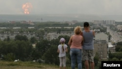 People watch the initial explosions on August 5.