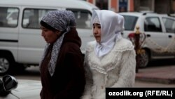 According to Uzbek authorities, if a head scarf is tied behind the head (like that of the woman on the left) that is socially acceptable. If the head scarf is tied under the chin that like that of the woman on the right, it is deemed to be offensive. (file photo)