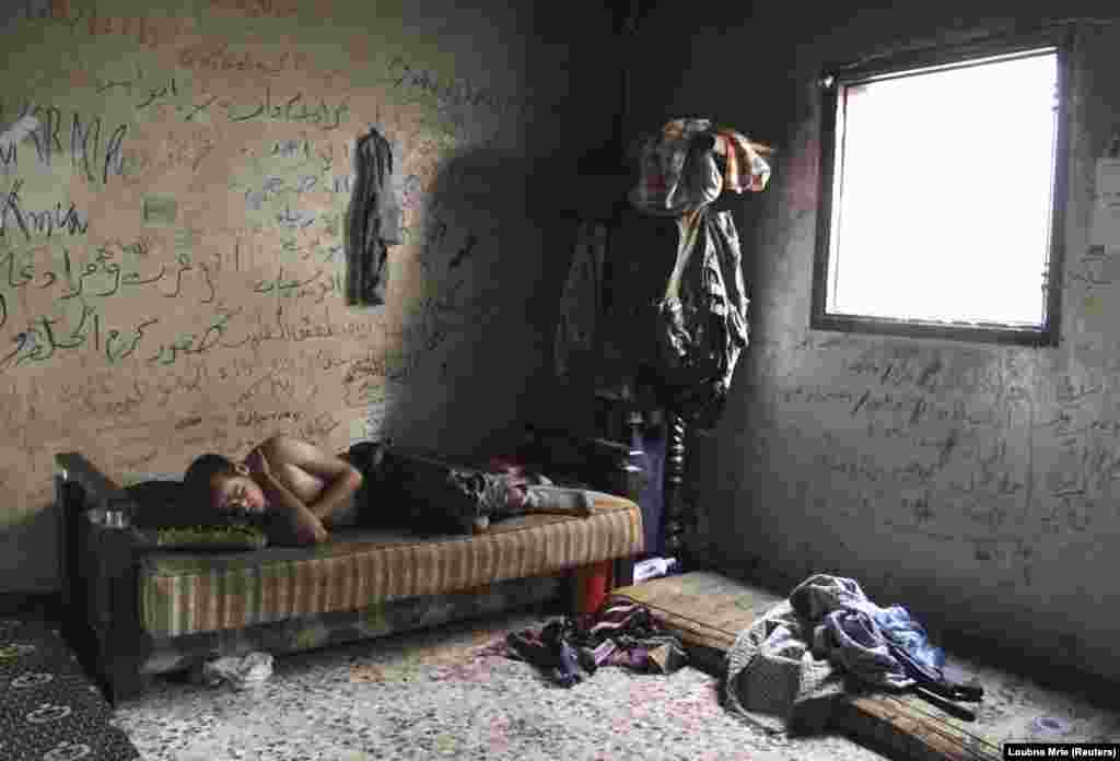 A Free Syrian Army fighter rests inside a house in Aleppo's Karm al-Jabal district. (Reuters/Loubna Mrie)