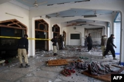 Pakistani security personnel inspect the Shi'ite Muslim mosque after the attack.