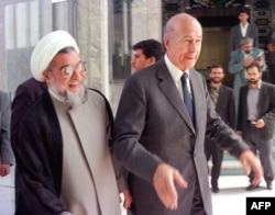 ژیسکار دستن در دیدار با حسن روحانی، دبیر وقت شورای عالی امنیت ملی ایران، در زمان سفر به تهران در بهار ۷۷