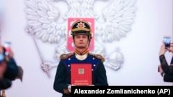 Орусиянын Конституциясын кармап турган аскер адамы.