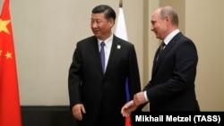 Председатель КНР Си Цзиньпин (слева) и президент России Владимир Путин.